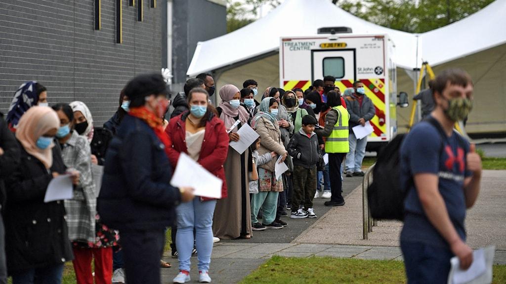 Människor köar för covid-vaccin i staden Bolton, Storbritannien.