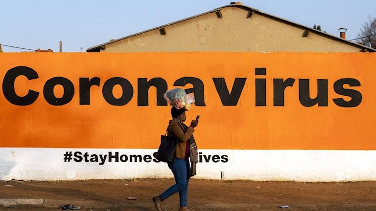 Kvinna går förbi banderoll om coronaviruset i Sydafrika.