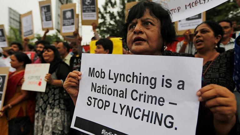 En kvinna i Ahmdabad i Indien protesterar mot lynchningarna.