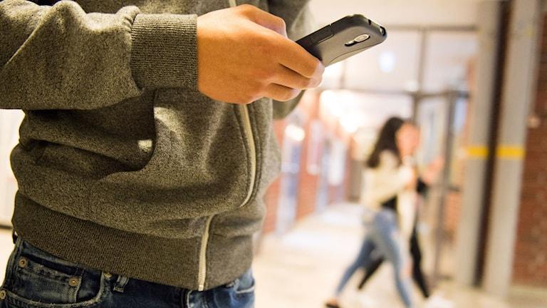Kille med mobiltelefon i skolan.