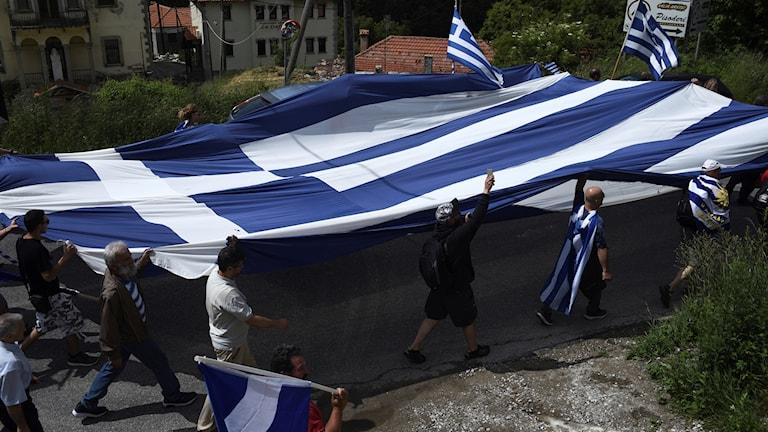 Grekisk flagga som bärs av demonstranter.