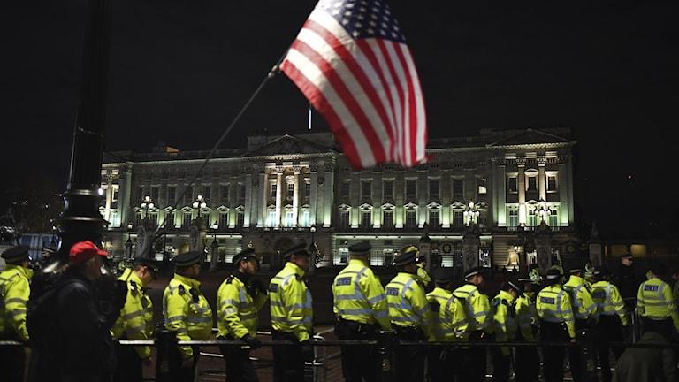 Polise och amerikanska flagga framför slott.