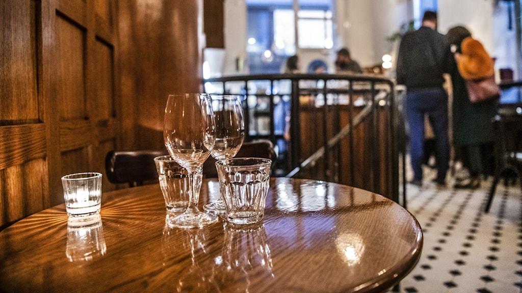 Glas står på ett bord i en restaurang. I bakgrunden syns kroggäster prata med varandra.