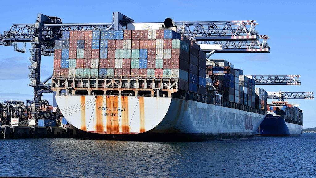 Containers lassas på ett fartyg.