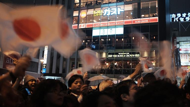 Människor viftar japanska flaggor