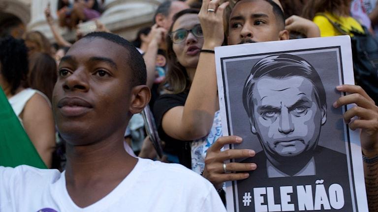 Demonstranter håller skylt med texten Inte han i en protest mot Jair Bolsonaro.