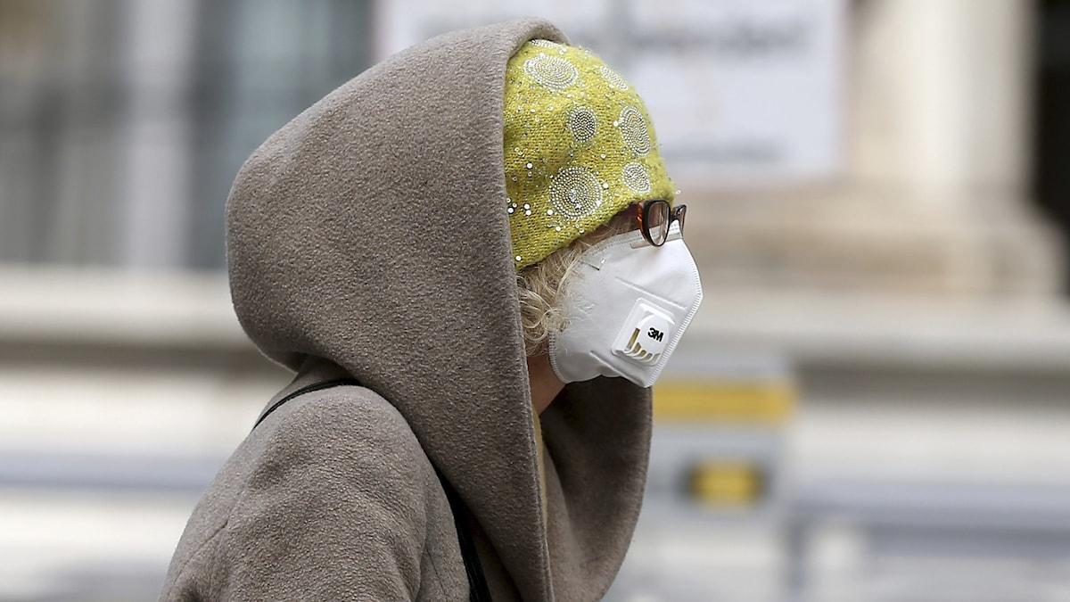 En kvinna i profil som bär munskydd i Wien, Österrike. Hon har en gul mössa och glasögonen; en kappa med luvan på.