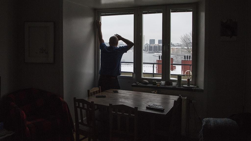 Deprimerad man står och tittar ut genom fönster