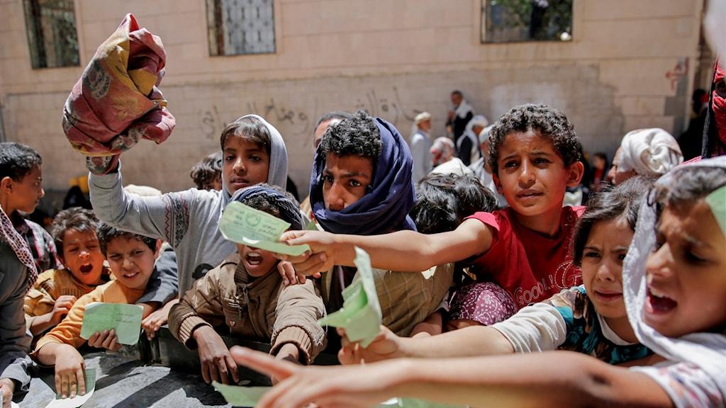 Jemeniter visar upp dokument som gör att de kan få ta emot matransoner av en lokal hjälporganisation.