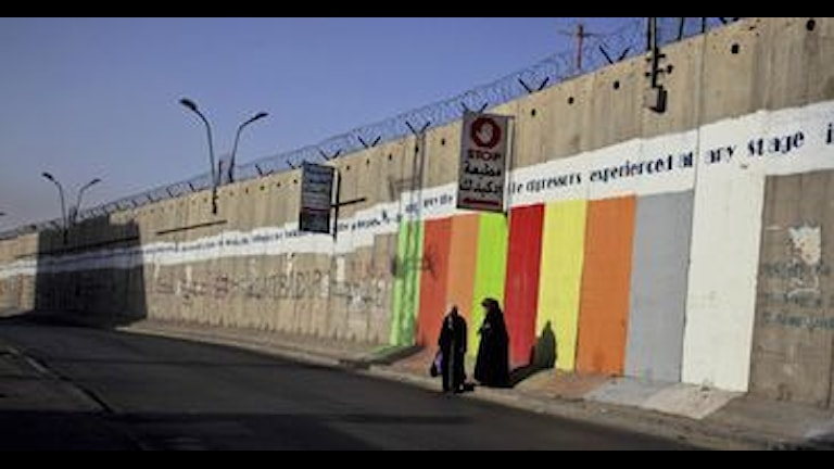 Palestinska kvinnor väntar på tranport vid Israels separationsbarriär i Aram på Västbanken. Foto: Muhammed Muheisen/Scanpix