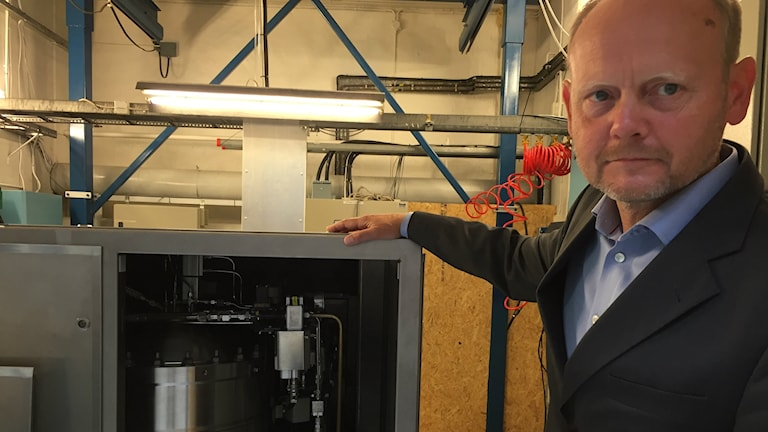 Bilden visar Gunnar Wieslander, vd för Saab Kockums, som står vid sidan av ett öppnat kabinett med en Stirlingmotor. Foto: Anna Bubenko/Sveriges Radio.