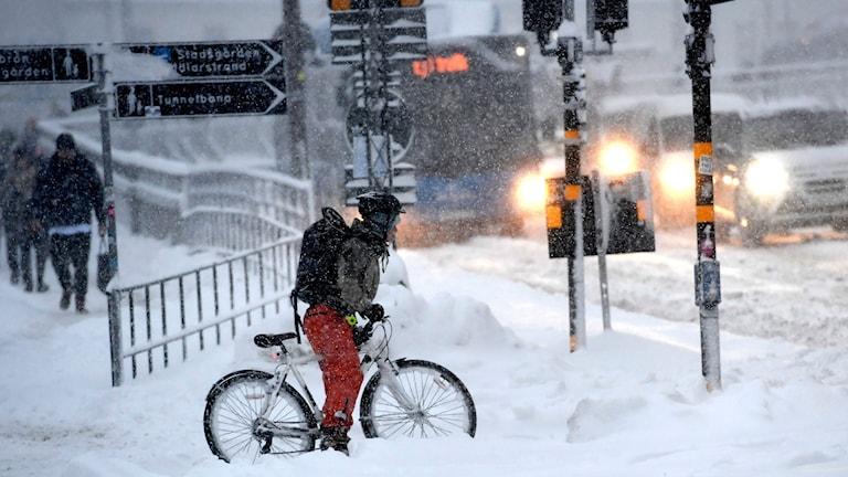 En cyklist på på en snöfylld gata vid Slussen i centrala Stockholm.