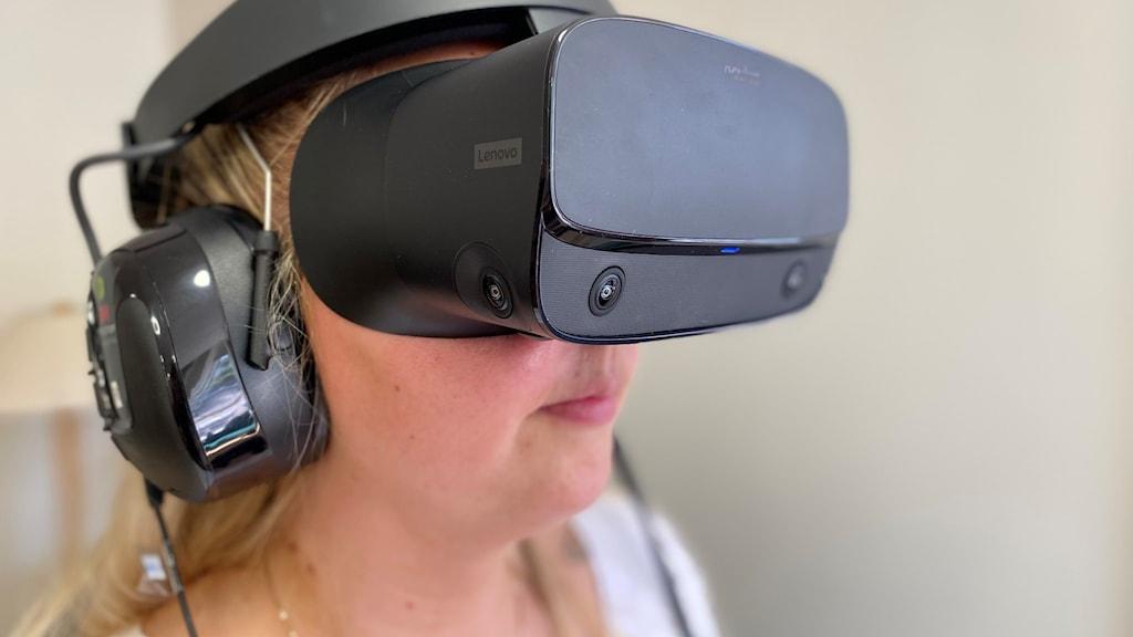 Kvinna med VR-glasögon över ögonen.