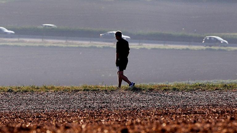 En man promenerar över en åker.