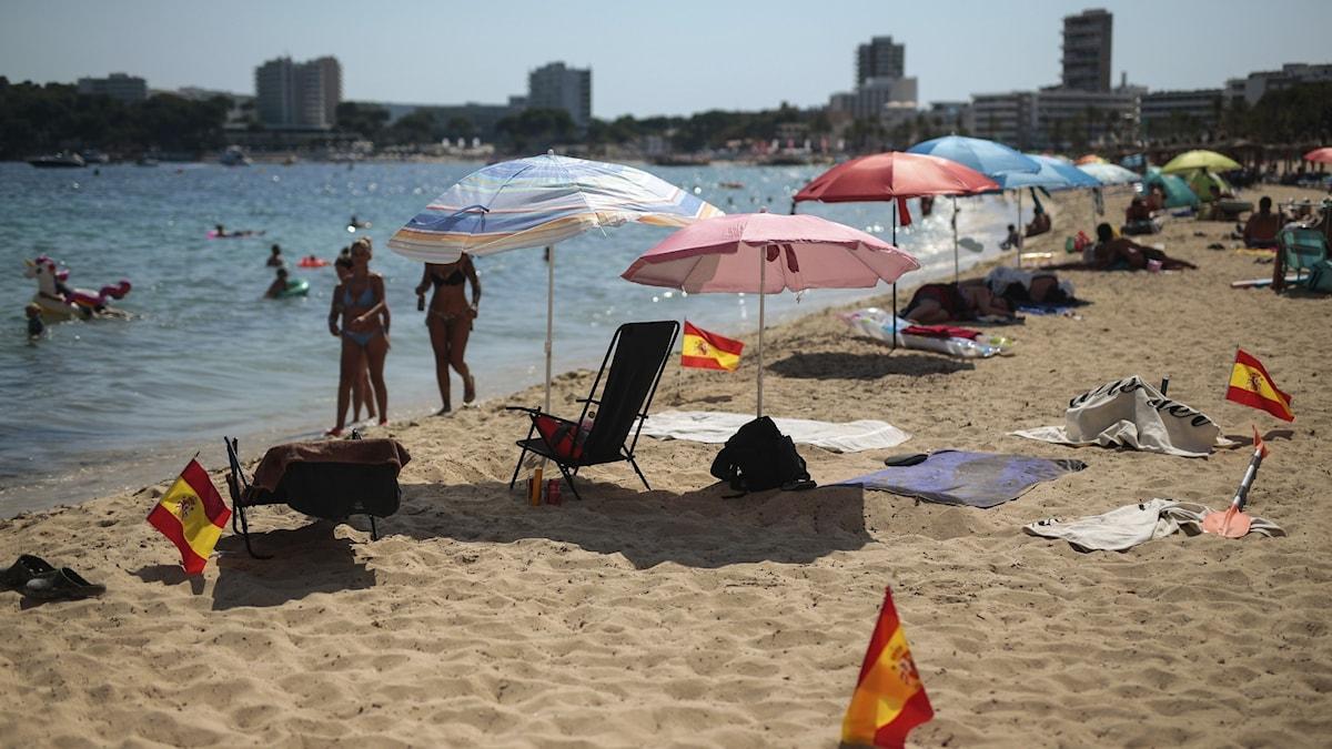 strand på mallorca med parasoll och spanska flaggor