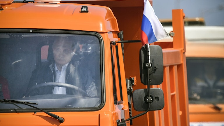 Vladimir Putin i en orange lastbil.