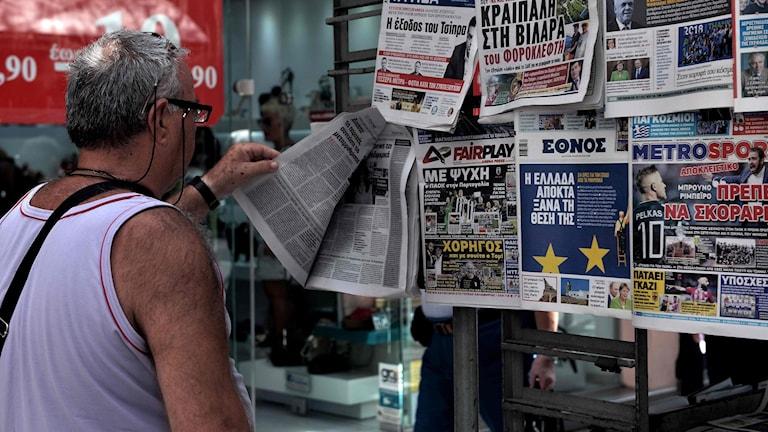 En man läser tidningen utanför en kiosk i Thessaloniki
