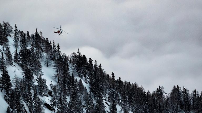 En räddningshelikopter söker igenom ett område i samband ned en tidigare lavinolycka i Valaiskantonen. Arkivbild.