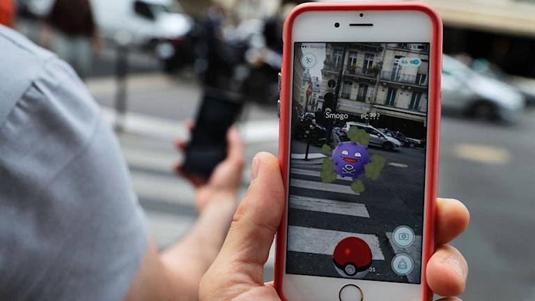 En hand som håller i en iphone. Den spelar Pokémon-go.