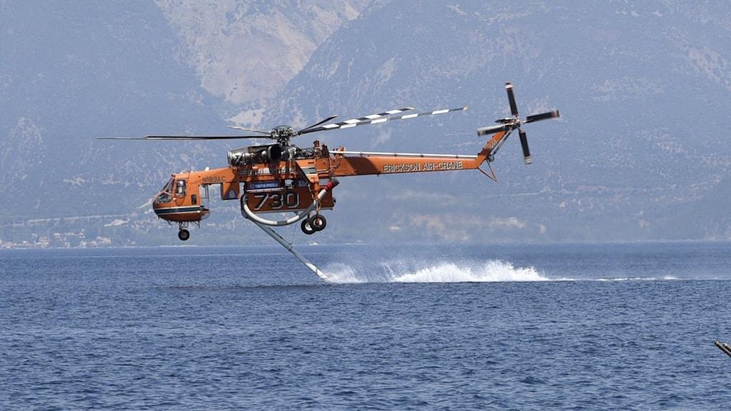Gul helikopter flyger över havet