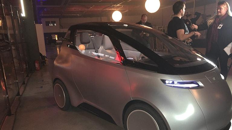 Bilden visar ett utställningsexemplar av företaget Unitis nya elbil. I bakgrunden intervjuas företagets vd Lewis Horne av en tv-reporter. Foto: Anna Bubenko/Sveriges Radio