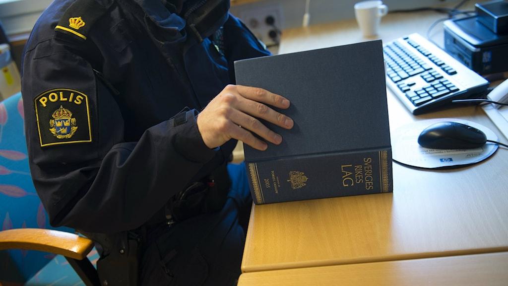 Bilden visar en polis som slår i en lagbok, sittandes vid sin dator. Foto: Fredrik Sandberg/TT.