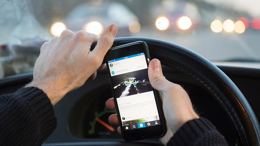 Bilförares hand som håller i en mobiltelefon och i ratten samtidigt.