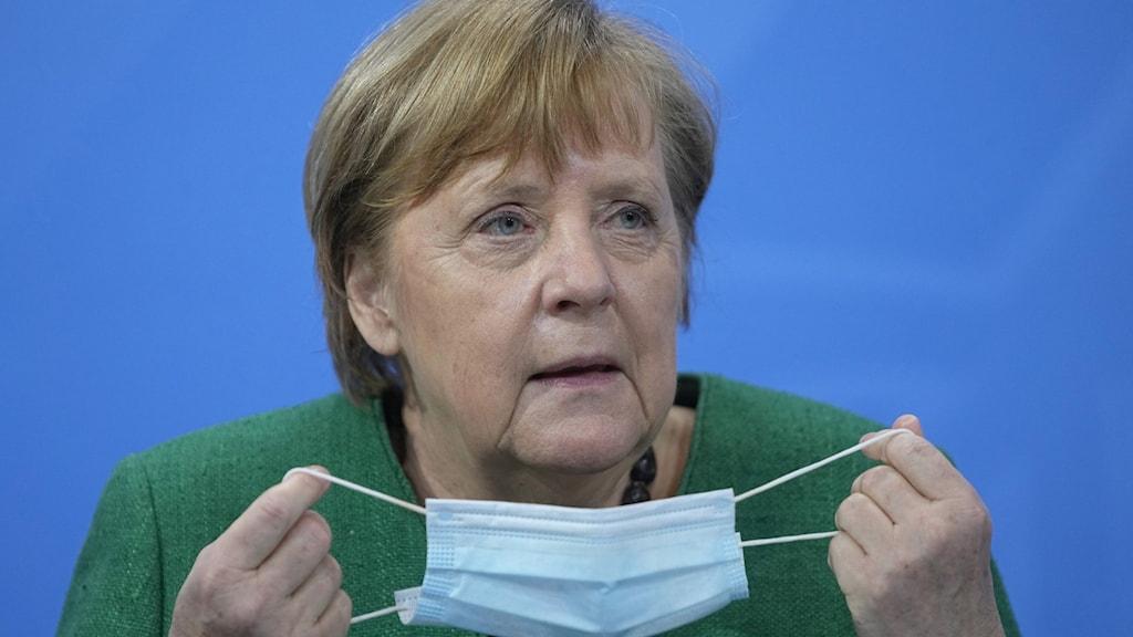 Angela Merkel håller i ett munskydd.