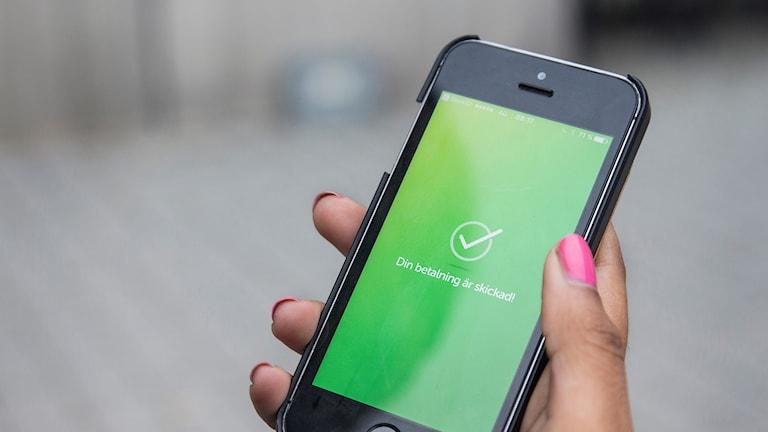 Hand som håller i en mobiltelefon.