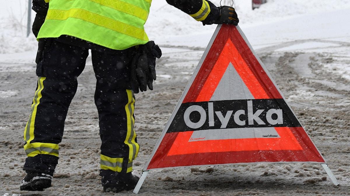 """En person i reflexväst sätter ut en varningsskylt med texten """"Olycka"""" på en snömoddig väg."""