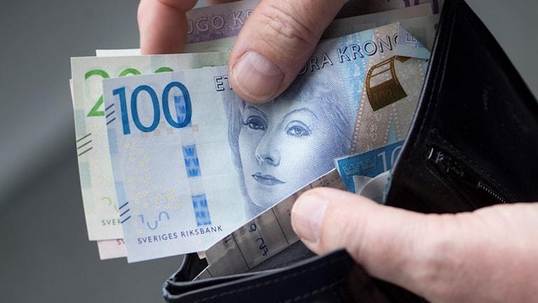 Person tar upp bunt med sedlar ur en svart plånbok.