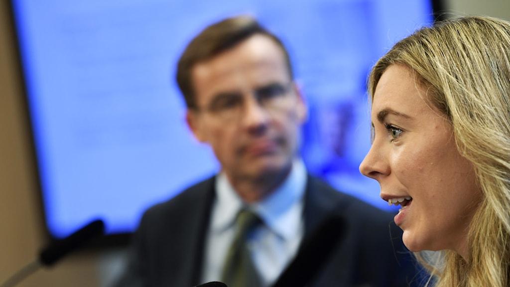 Blond kvinna i förgrund och mörkhårig man med glasögon i bakgrund.