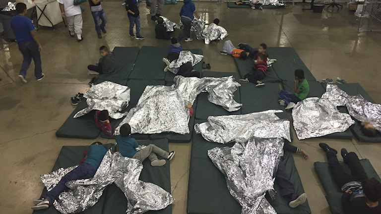 Barn som ligger på golvet under filtar