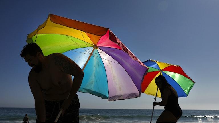 Bilden visar siluetterna av en man och en kvinna som sätter upp varsitt färgglatt solparasoll på en strand. Foto: Jae C. Hong/AP/TT