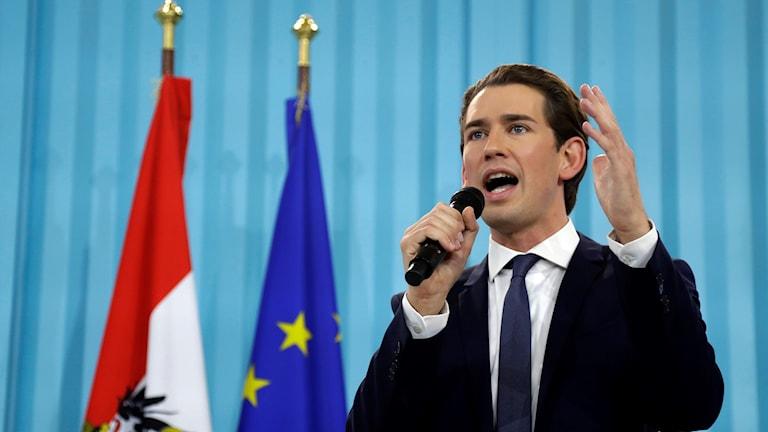 Man framför en österrikisk och en EU-flagga.