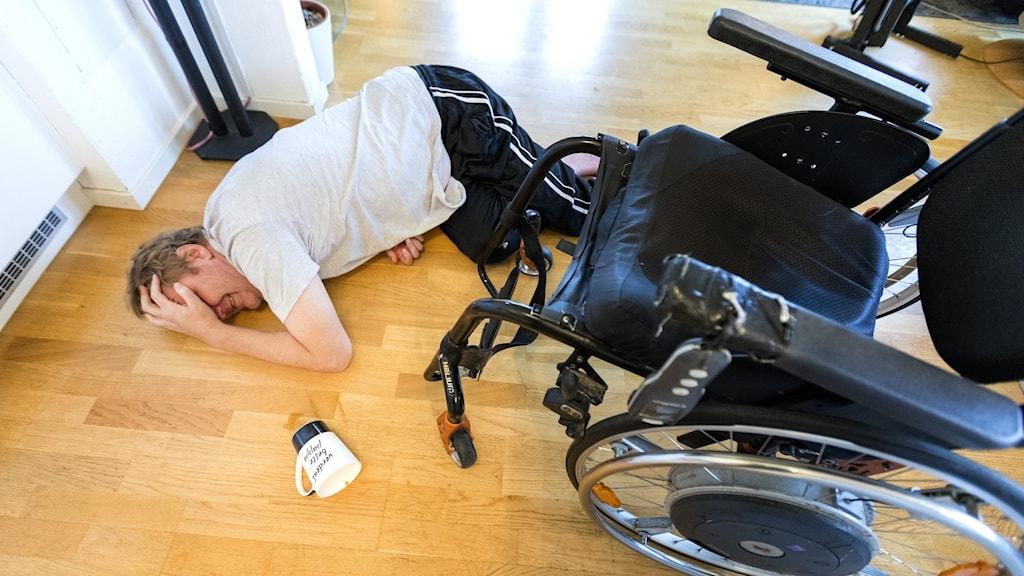 Man som ligger på golvet bredvid sin rullstol.