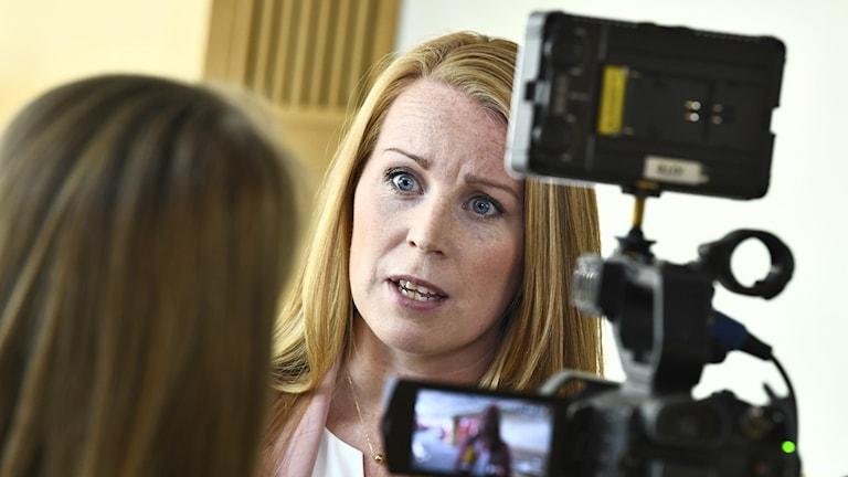 Bild på kvinna i långt rött hår som intervjuas med mikrofon.