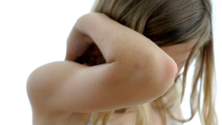 Flicka som håller armbågen som skydd för ansiktet.