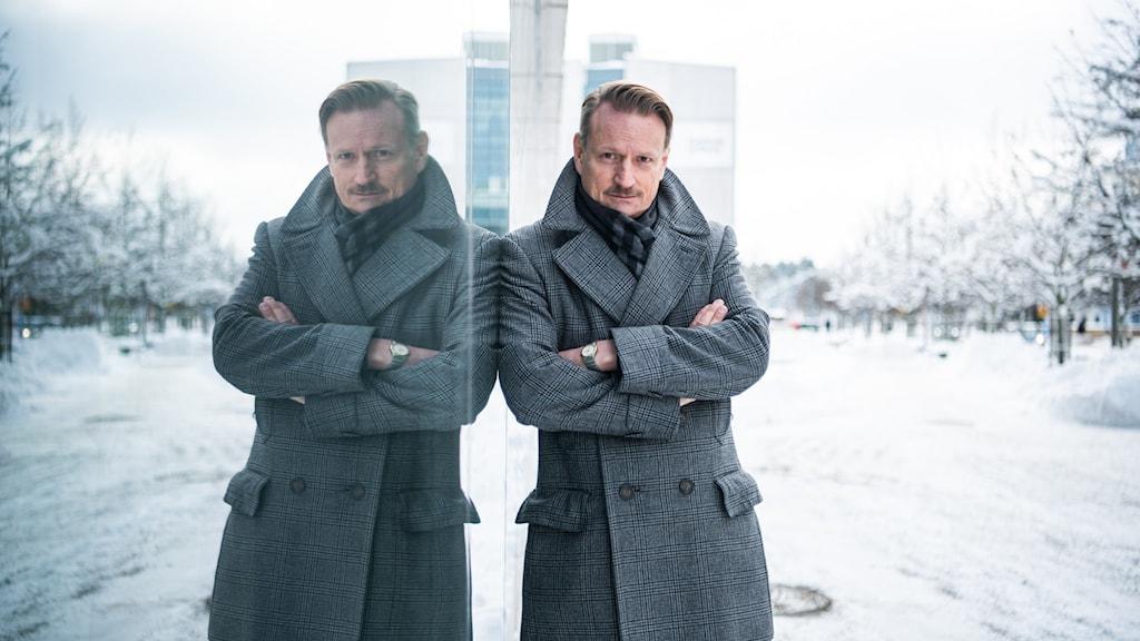Matti Sällberg i grå rock som går till halva låret. Han står lutad mot sin egen spegelbild vid en spegelvägg. Vinter och snö runtomkring-
