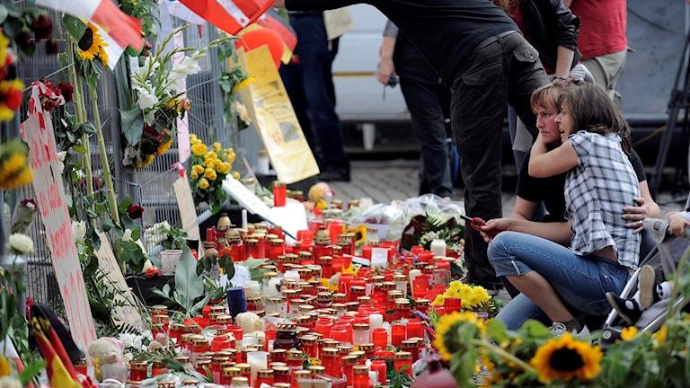 Blommor och ljus, personer som sörjer.