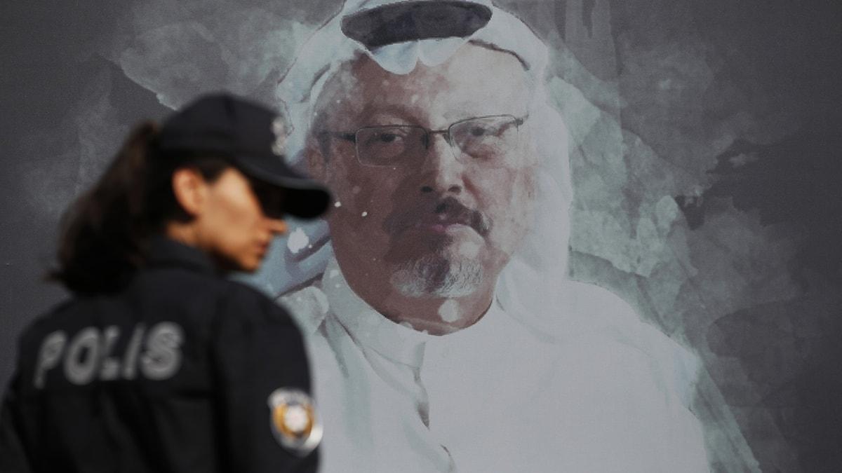 En kvinna i polisuniform framför en bild av mördade journalisten Jamal Khashoggi.