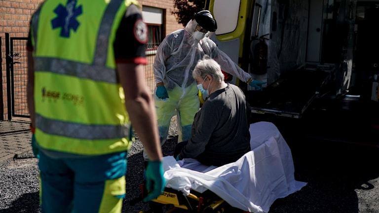 Belgisk vårdpersonal hämtar patient med misstänkt coronasmitta med ambulans.