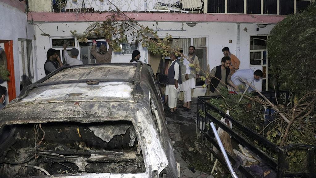 En bombad bil på en innergård i Kabul och afghaner som rensar upp efter en drönarattack från USA.
