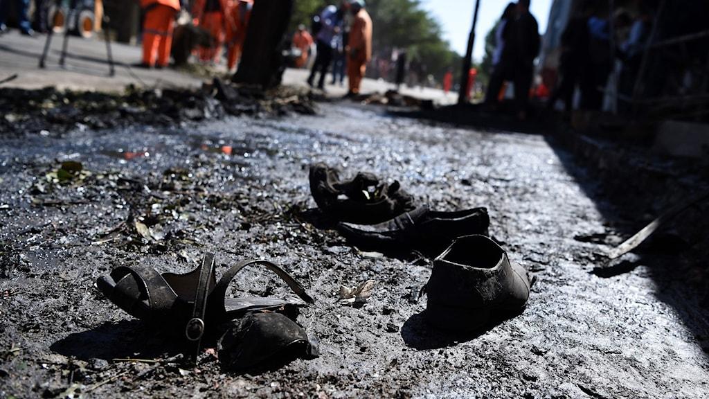 Två par skor på marken nära attentatsplatsen