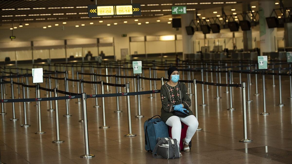 En ensam kvinna väntar vid incheckningen på Zaventem-flygplatsen i Europa. Resandet i Europa sjunker från redan rekordlåga nivåer.