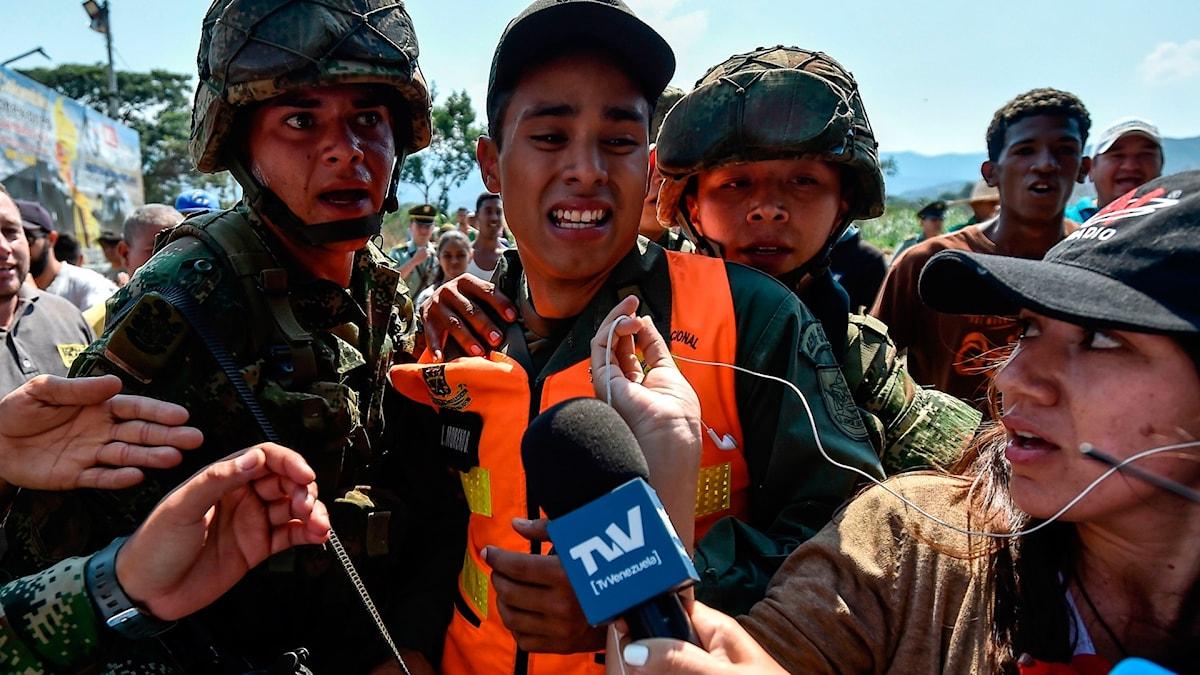 Colombianska soldater eskorterar en man från den bolivarianska armén i Venezuela som deserterat och tagit sig till Colombia.