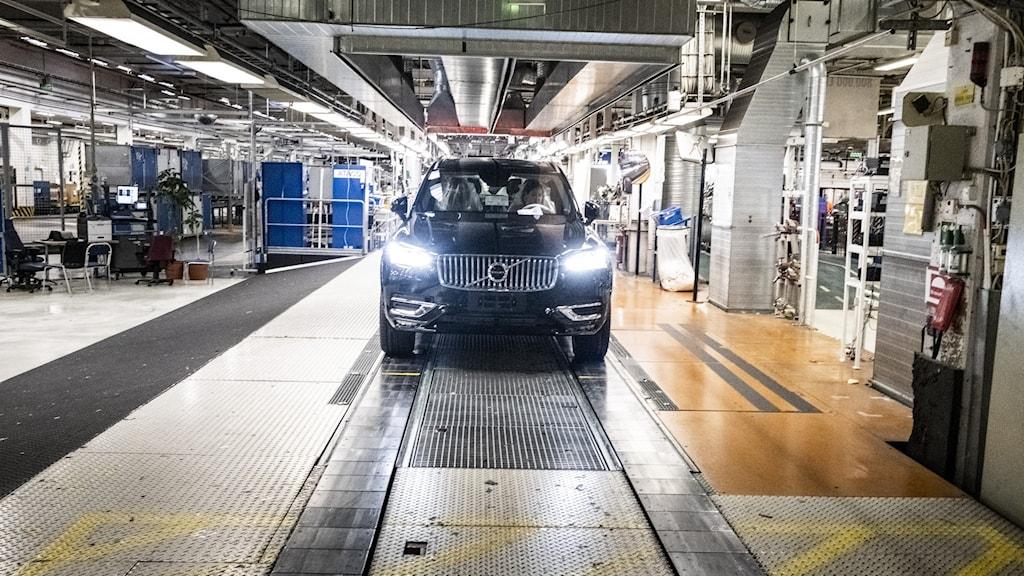 En svart Volvo-bil med lamporna tända rullar av produktionslinan i fabriken i Göteborg.