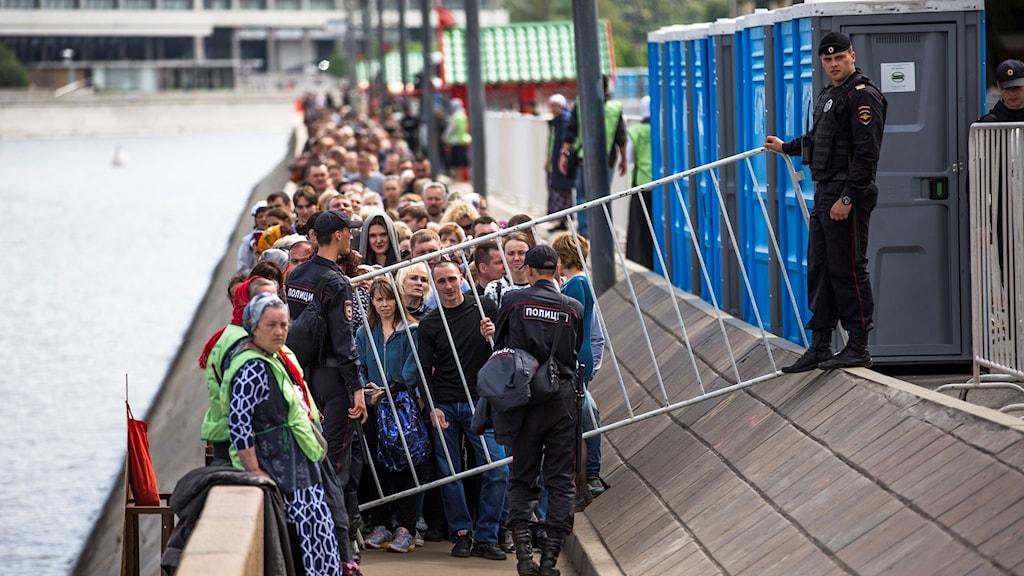 Människor köar bakom ett staket.