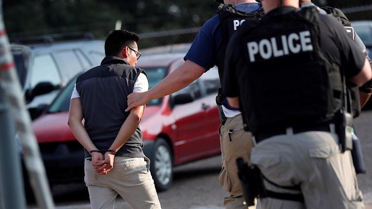 Ryggar på tre män varav tre är poliser och en är gripen man med handfängsel