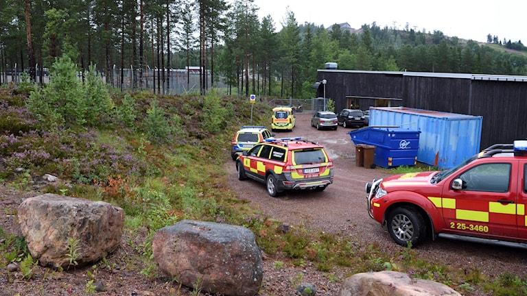 Polisbilar och räddningsfordon står utanför ett staket.